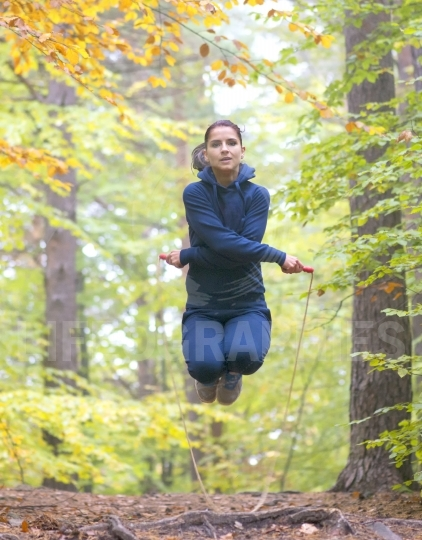 Young beautiful fitness woman skipping rope in forest, autumn co