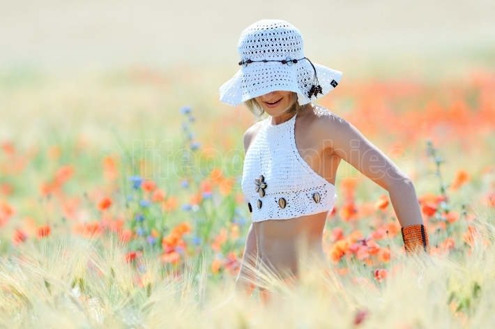 Young beautiful woman on golden wheat field in summer sunny day