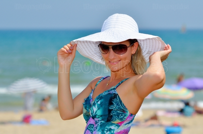 Young beautiful woman relaxing on the beach in summer