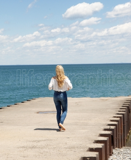 Young blond woman walking on a pier.