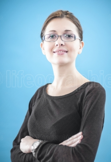 Young business woman standing with folded hands