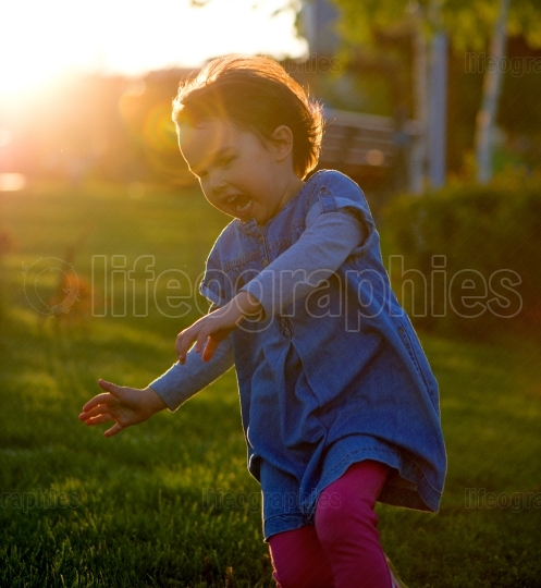 Young child running through grass in park