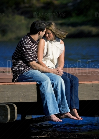 Young Couple In Love Hold Hands On Dock At Lake