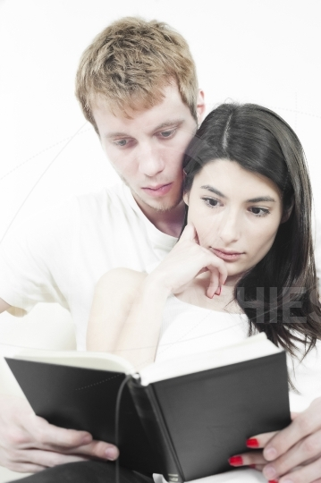 Young couple resting at home couch, reading book, embracing.