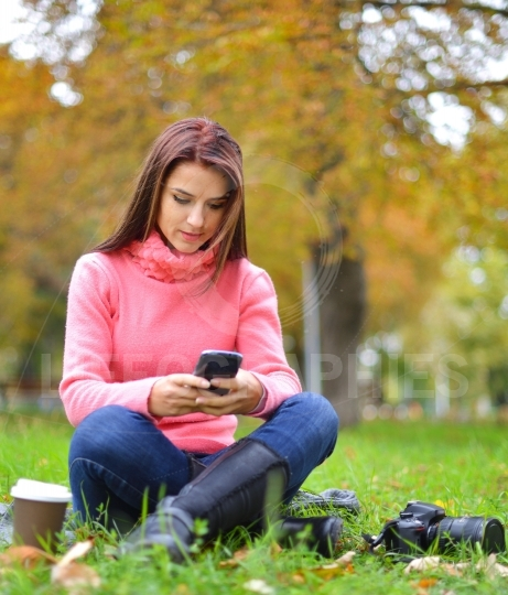 Young fashionable teenage girl with smartphone, camera and takeaway coffee in park in autumn sitting at smiling. Woman in fall in park texting