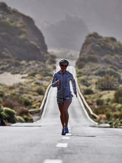Young Female Traveler running on the road in Teide volcano crate