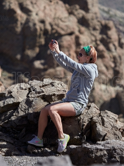 Young female traveler taking selfie on the beautiful rocky backg