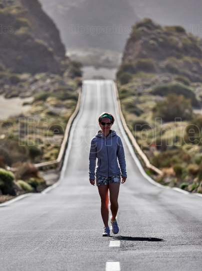 Young Female Traveler walking on the road in Teide volcano crate