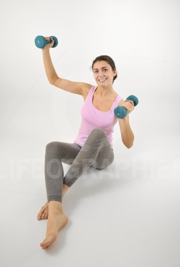 Young fit woman lifting dumbbells