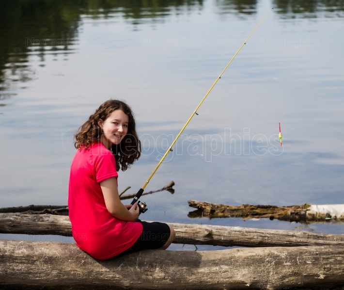 Young girl relaxing while fishing the lake