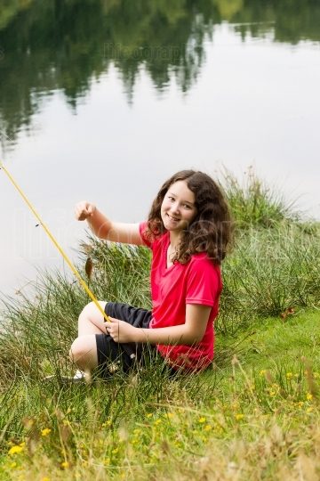 Young Girl Sitting Down and Catching Fish on the Lake