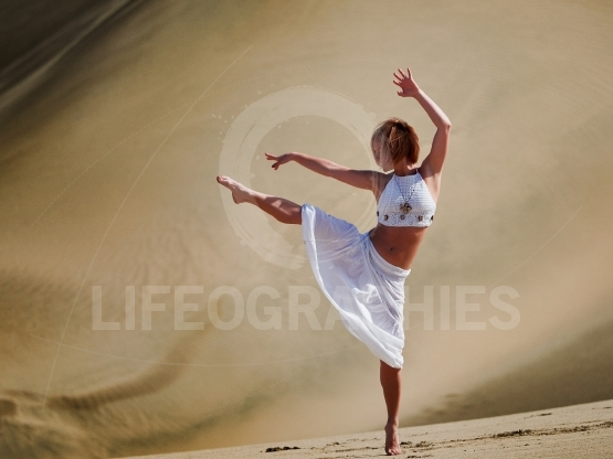 Young happy woman dancing on sand dunes in summer