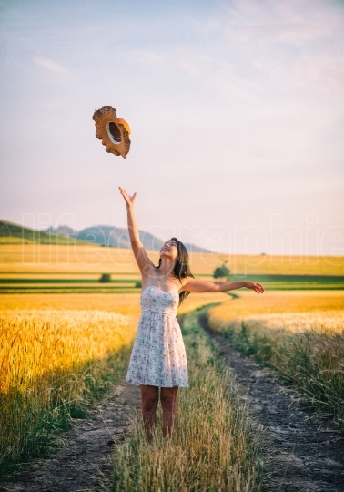 Young happy woman in a wheat field with white dress and summer hat