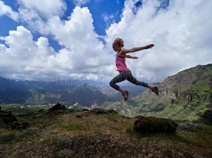 Young happy woman jumping on top of the mountain