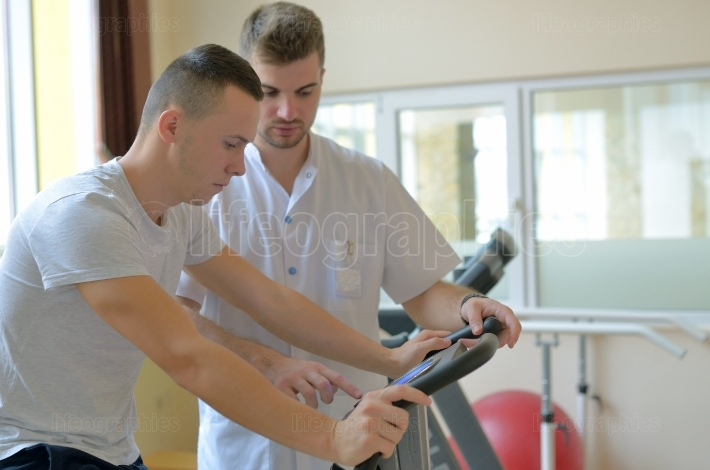 Young man on exercise bicycle with instructor