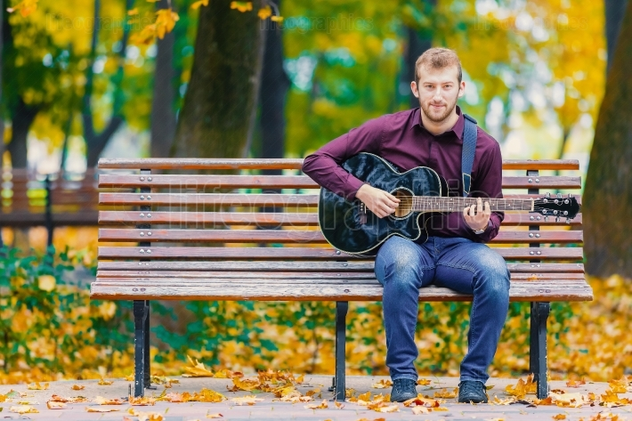 Young man standing in park with guitar
