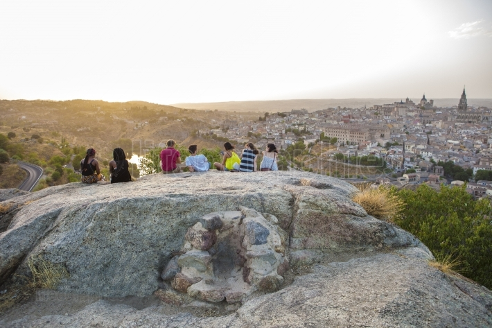 Young people sitting on the stone enjoying peaceful magic moment