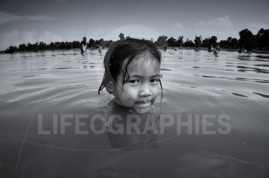Young poor girl from cambodia playing in a dirty lake