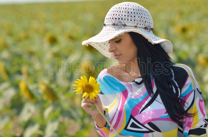 Young pretty woman on blooming sunflower field in summer