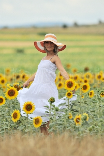 Young smiling woman on blooming sunflower field in summer