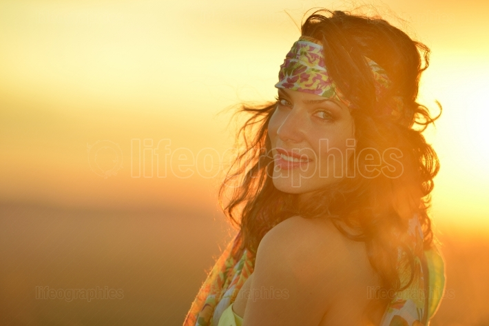 Young smiling woman outdoor in summer sunset light