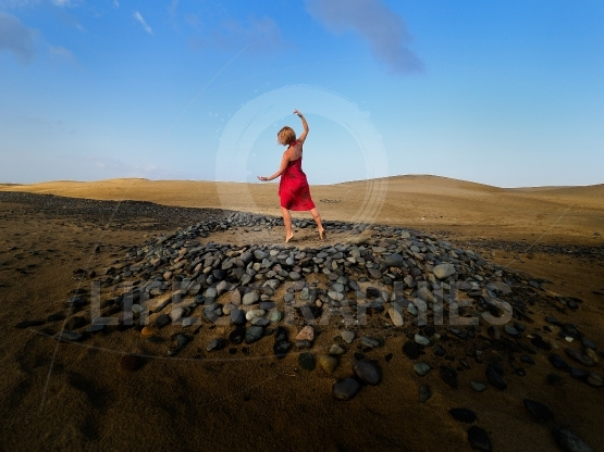 Young woman dancing on sand dunes in summer
