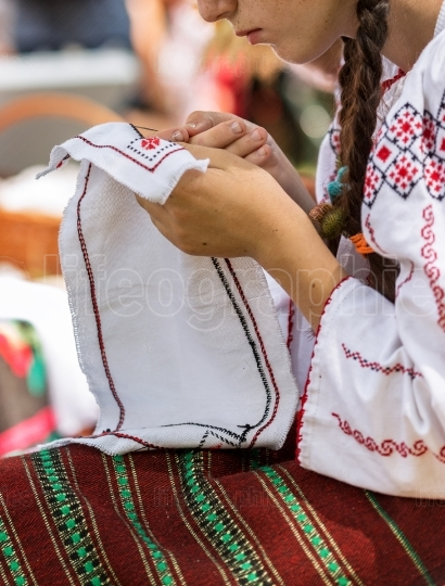 Young woman dressed in a romanian folk port, working manually at