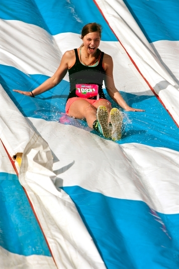 Young Woman Enjoys Going Down Slide In Obstacle Race