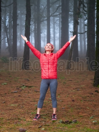 Young woman exploring stunning autumn foggy forest in the mounta