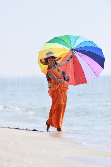 Young woman holding colorful umbrella on the beach in summer