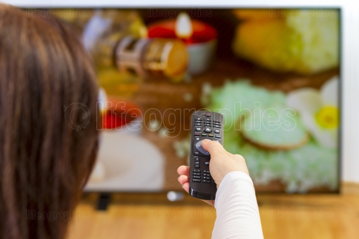 Young woman holding tv remote and surfing programs