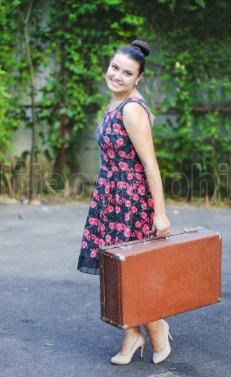 Young woman in vintage skirt with an old suitcase