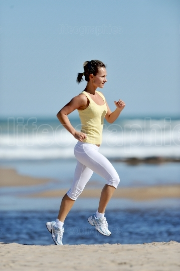 Young woman jogging on the beach in summer sunny day