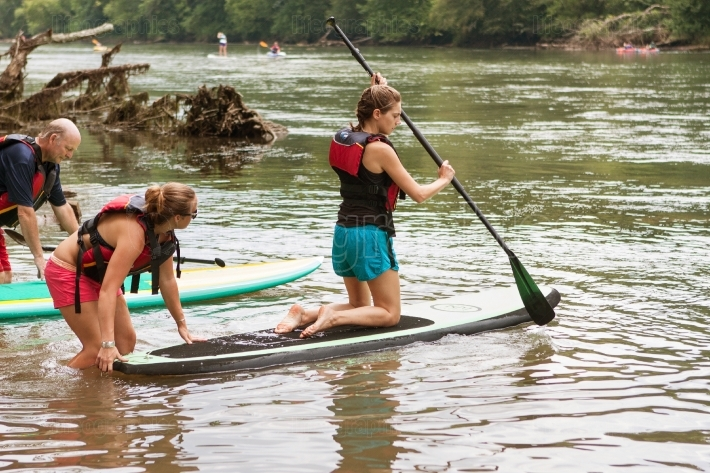 Young Woman Kneels On Paddleboard In Chattahoochee River