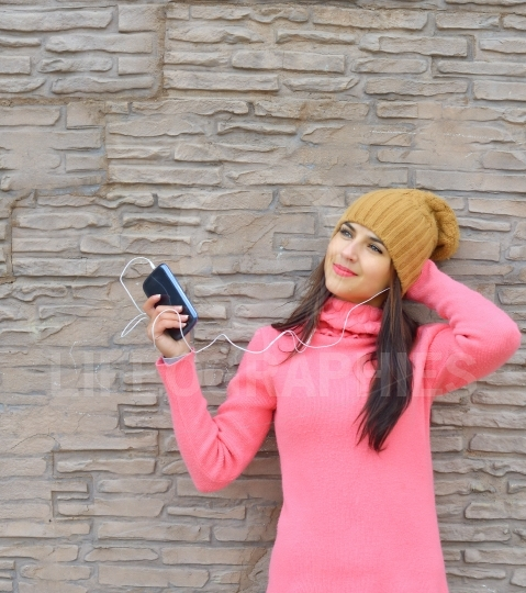 Young woman listening to music in headphones on brick wall background