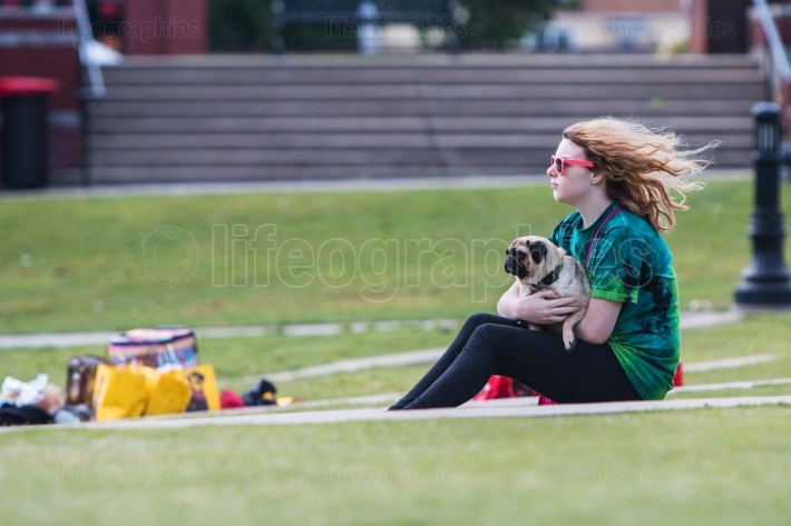 Young Woman Lovingly Holds Pug At Dog Festival Event