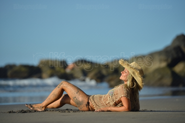 Young woman relaxing on the beach in summer day