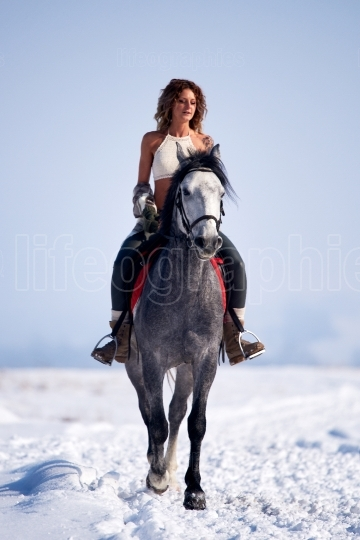 Young woman riding horse outdoor in winter