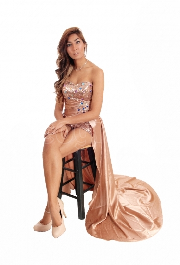Young woman sitting in prom dress.