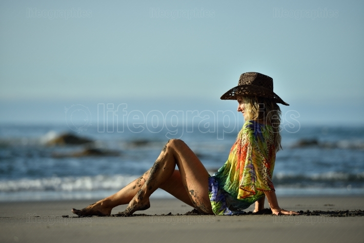 Young woman sitting on the beach in summer day
