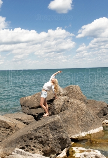 Young woman standing on big rock's