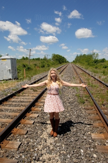 Young woman standing on railroad truck's.
