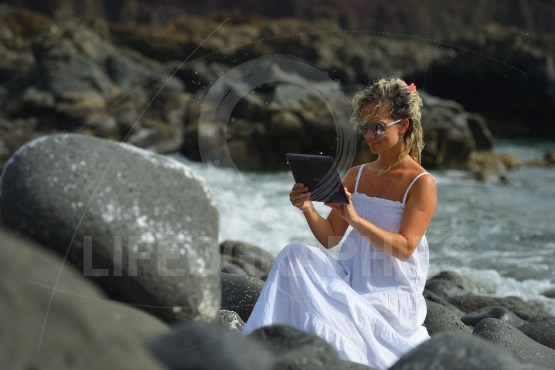 Young woman using tablet on black rocky beach in summer