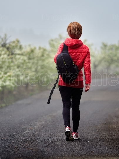Young woman walking through blooming orchard