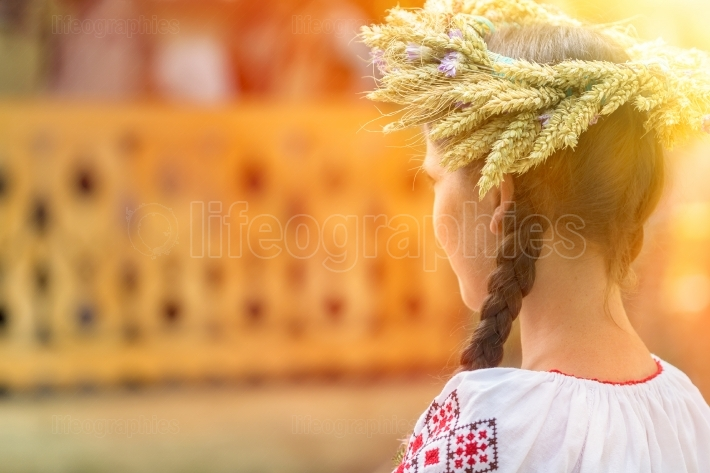 Young woman wearing a braiding crown made of wheat and flowers