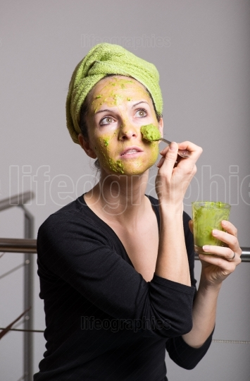 Young woman with an avocado facial mask
