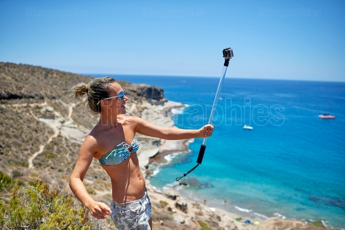 Young woman with gopro camera on mediterranean coast