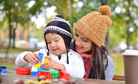 Young woman with her child playing with colorful plastic blocks outdoors