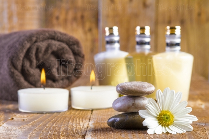Zen basalt stones and spa oil with candles on the wood