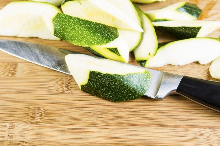 Zucchini Slices on Cutting board with Large Knife